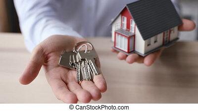 Realtor hand holding keys and tiny house layout closeup view...