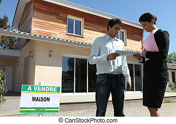 Realtor in front of house for sale