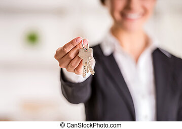 Realtor is giving the keys to an apartment to clients. Focus...