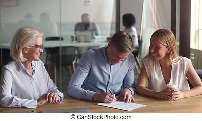 Senior realtor make real estate deal with happy young couple first time home buyers renters sign mortgage loan sale purchase contract, agent handshake property owners customers give keys to new house