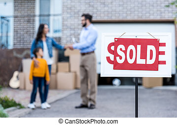 realtor making deal with single mother with sold signboard ...