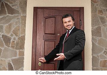 realtor opening wooden door and smiling welcoming. brown wooden door and business man in suit and tie