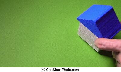 Realtor placing toy house with blue roof and small key against green background. Real estate deal concept. 4K shot
