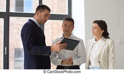 realtor showing office to customers with tablet pc