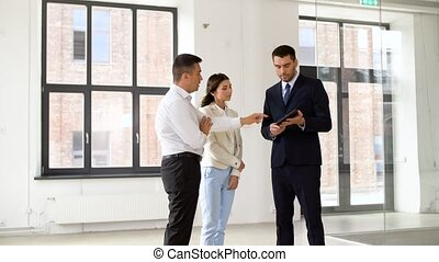 realtor showing tablet pc to customers at office - real...