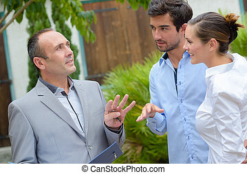 Realtor talking to young couple in front of property