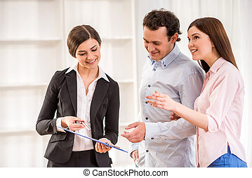 Realtor - Young couple are talking to real estate agent.