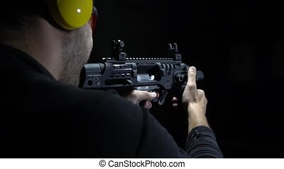 Rear angle of shooting bullets with gun in range - shooting...