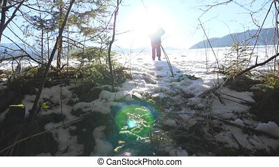 Rear back view of unrecognizable man jogging on snowy field near forest. Young hiker running on snow meadow at sunny day. Sun light at background. Concept of travel or journey. Slow motion