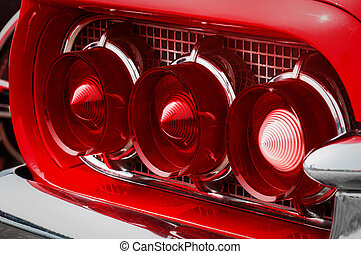 Rear cluster of an old timer luxury sports car with three tail lights with red and white glass cones, pipes framed in chrome nozzles on the shiny metal grid panel
