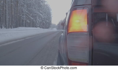 Rear lamp SUV on winter road, red light. Close up of Big...