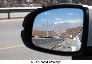 Rear mirror view of a road in Oman