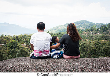 Rear of family sitting on the stone natural background