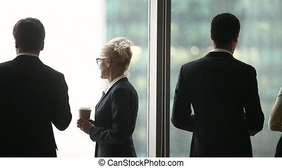 Rear side view multinational businesspeople talking standing near panoramic window
