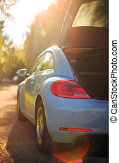 Rear side view of car in sunlight on the path with opened trunk. Photography about travelling