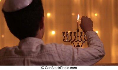 rear view a Jewish boy lights a third menorah candle during the Jewish holiday of Hanukkah