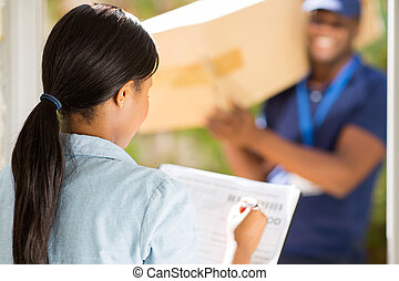 african woman signing receiving paper - rear view african...