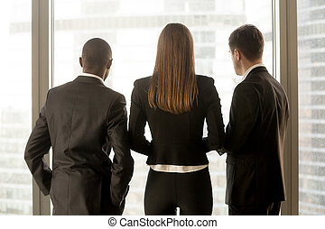 Rear view at african and caucasian businesspeople standing near