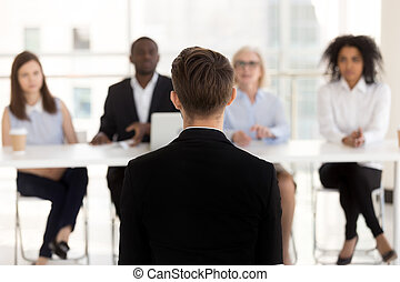 Rear view at job seeker during interview with hr team