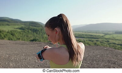 Rear view. Athlete girl jogging in mountains at sunset running from the camera and listen to music in headphone on a smartphone. Sportswoman listening to music during evening running training . Healthy Lifestyle