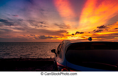 Rear view blue compact SUV car with sport and modern design parked on concrete road by the sea at sunset. Electric car technology and business. Hybrid auto and automotive. Tropical road trip travel.