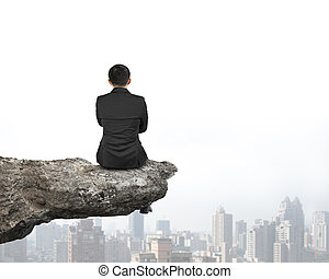Rear view businessman sitting on cliff with urban skyscrapers