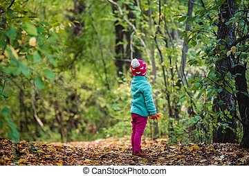 Rear view child looking forward standing alone in forest