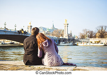 rear view. couple of lovers on Seine river in Paris. travel in spring in Europe.