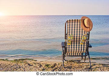 Rear view deck chair with accessories in the evening.