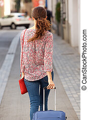 Rear view female traveler walking on the street with bag