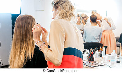 Rear view image of professional makeup artist working with model