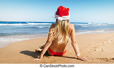 Rear view image of sexy young woman in Santa hat and bikini sitting on the beach. Concept of travel and tourism on Christmas, New Year and winter holidays.