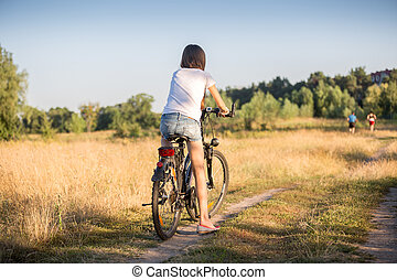Rear view image of young girl riding bicycle on countryside road