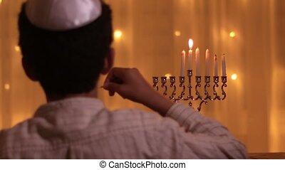rear view jewish boy lights fifth menorah candle during jewish holiday Hanukkah 4k