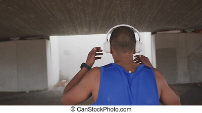 Rear view man with prosthetic leg listening to music - Rear ...