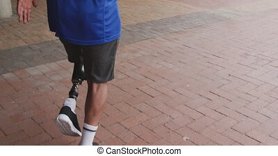 Rear view man with prosthetic leg running - Rear view close ...