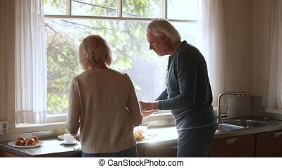 Rear view mature couple cooking together and dancing in kitchen