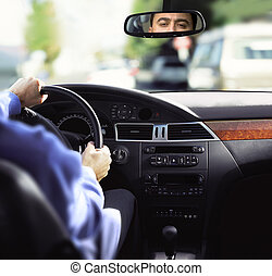 rear-view mirror and dashboard - man sits on driver\'s seat...