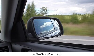 Rear view mirror of the car at the summer day
