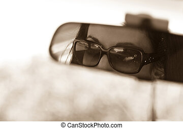 Rear View Mirror - The face of a young woman driving as seen...