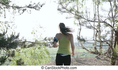 Rear view. Mountain landscape. Caucasian running girl. Jogging in the morning at forest in mountains. Athletic run