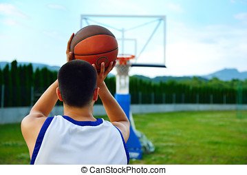 Rear view of a basketball player, shooting at basket outdoor