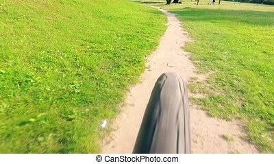 Rear view of a bicycle moving fast along park trail - Rear...