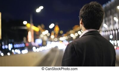 Rear view of a businessman looking at cars passing by in a night city