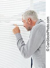 Rear view of a businessman peeking through blinds