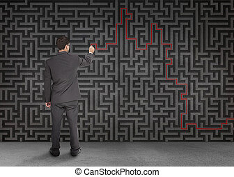 Rear view of a businessman writing a red line through black maze on a wall