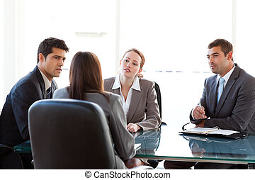 Rear view of a businesswoman being interviewed by three...