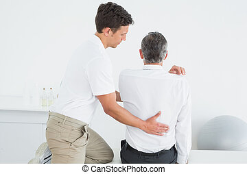 Rear view of a chiropractor examining man - Rear view of a...