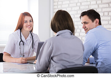 Couple Sitting In Front Of Female Doctor