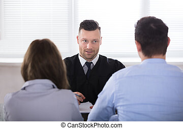 Couple Sitting In Front Of Judge